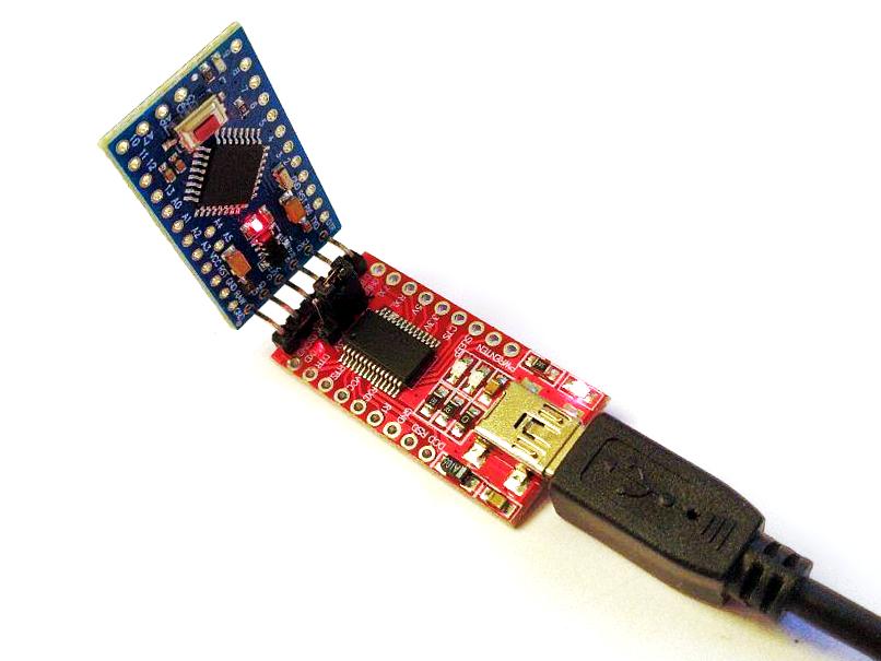 Zdjęcie płyty Arduino Pro Mini połączonej przez piny programatora do modułu FTDI konwertera sygnału USB do szeregowego UART połączony do komputera przez kabel mini USB.